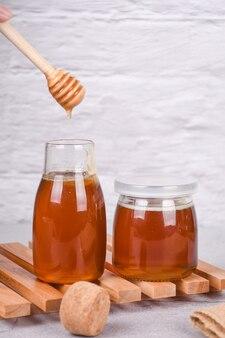 木製のテーブルに木製のハニーディッパーと蜂蜜