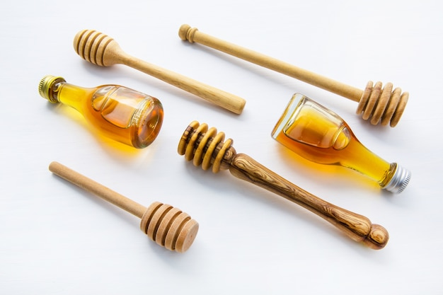 Honey wooden dipper and little honey bottle on white wooden background.
