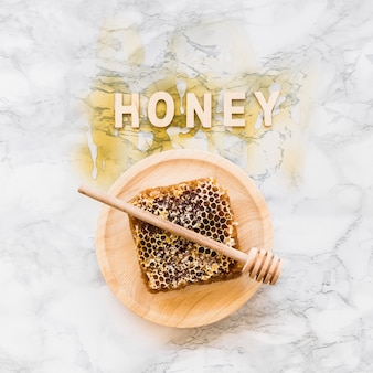 Honey word over the honeycomb with dipper on wooden plate