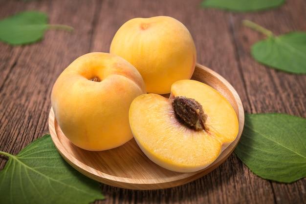古い木製のテーブルに蜂蜜イエローピーチ、木製のテーブルに木の板に新鮮な韓国の桃、ぼかしテーブルに黄色の桃。