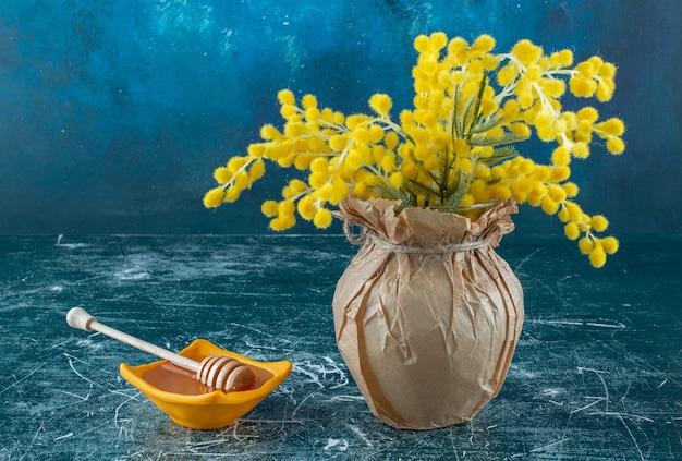 Miele in un piattino giallo su sfondo blu. foto di alta qualità