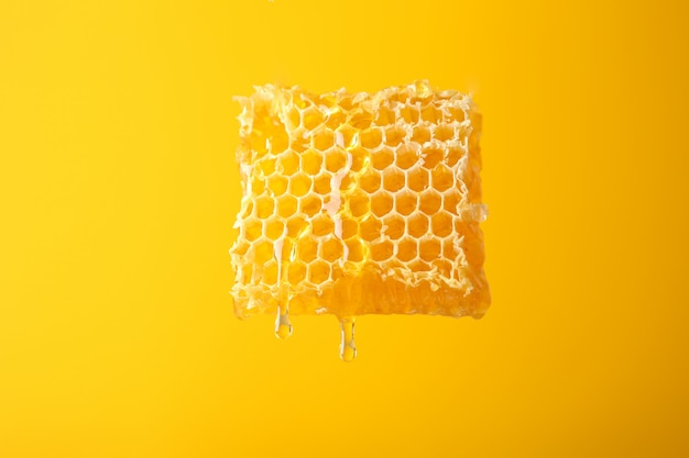 Honeycomb against yellow background, copy space