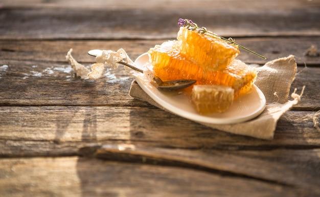 ハニカムと木製の蜂蜜ディッパー。生の蜂蜜。自然な蜂蜜、クローズアップビュー