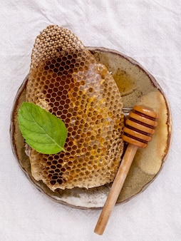 Honeycomb in ceramic plate and dipper on fabric background.