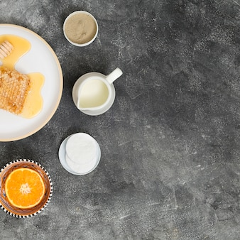 Honeycomb on ceramic plate with halved orange; cotton pads; pitcher of milk and rhassoul clay on black concrete backdrop