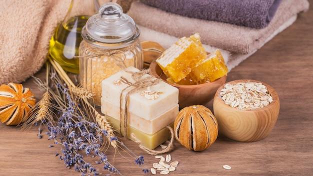 Соты, косметическое масло, морская соль, овес и мыло ручной работы с медом на деревенском деревянном фоне. натуральные ингредиенты для домашней маски или скраба для лица и тела. уход за здоровой кожей. концепция спа.