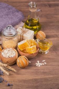 素朴な木製の背景に蜂蜜、化粧品オイル、海塩、オーツ麦、蜂蜜と手作り石鹸。自家製フェイシャルおよびボディマスクまたはスクラブ用の天然成分。健康的なスキンケア。 spaのコンセプト。