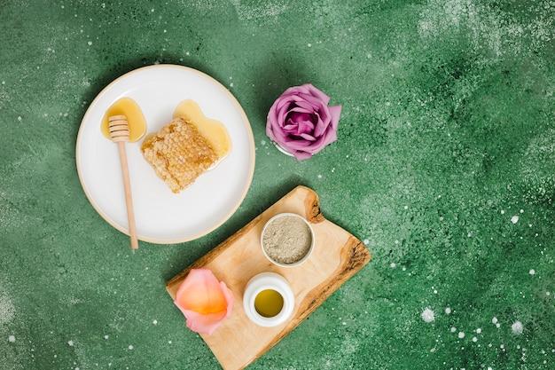 Сотовый ковш; мед; лепесток розы; глина и порошок rhassoul на зеленом текстурированном фоне