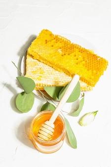 ハニカム、蜂蜜、蜜蝋。健康的で美しいライフスタイルのための天然有機養蜂製品。ハードライト、暗い影、白い漆喰の背景、上面図