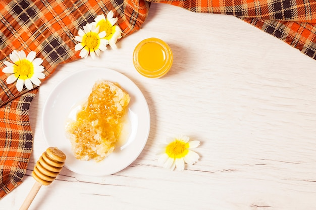 Honeycomb and honey with checkered table cloth on wooden desk