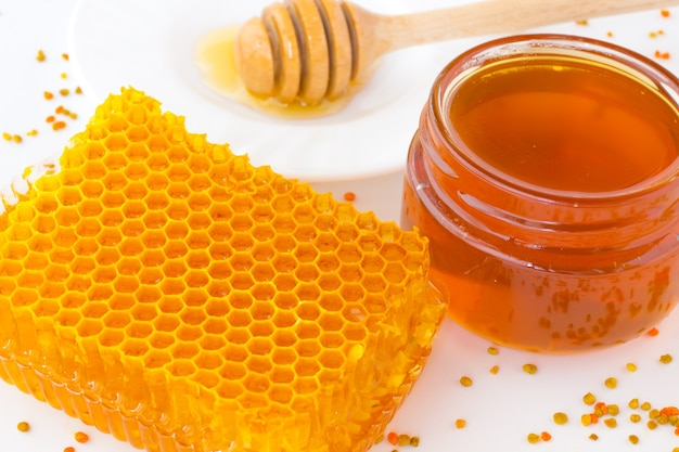 Honeycomb and jar of dark honey.  flower pollen is scattered on  white