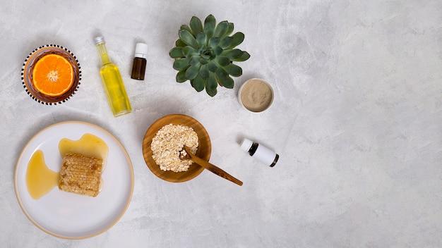 Favo; avena; olio essenziale; pianta di cactus; argilla rhassoul; agrumi tagliati a metà su sfondo bianco con texture in cemento