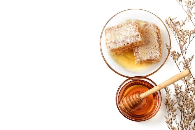 Соты на блюде с медовым ковшом и сухим цветком, изолированными на белой стене и копией пространства, продукты пчеловодства по концепции органических натуральных ингредиентов