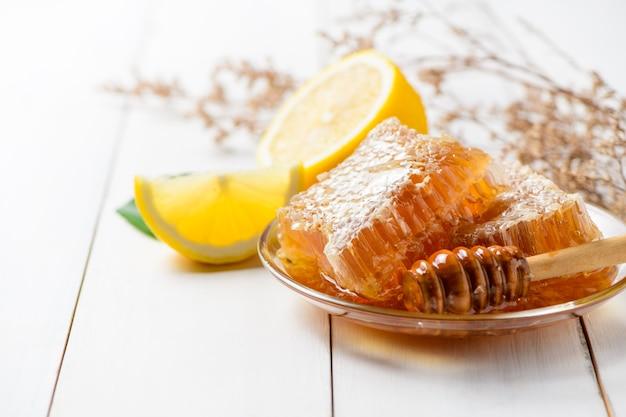 레몬 꿀 국자와 함께 접시에 벌집, 유기농 천연 재료 개념으로 꿀벌 제품
