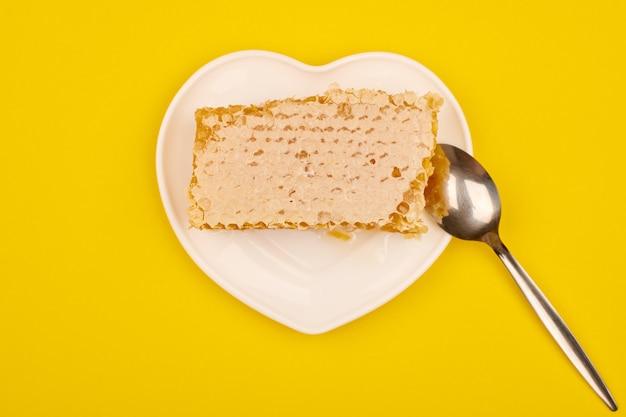 접시에 벌집, 달콤한 개념입니다. 맛있는 라임 꿀, 노란색 배경. 과자에 대한 사랑.