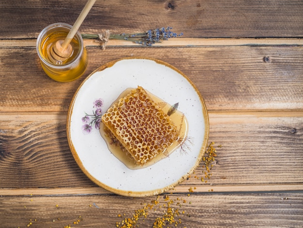 Honeycomb piece on white plate with honey pot over the wooden table