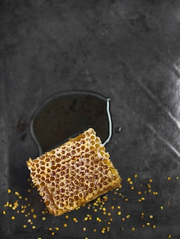 Honeycomb piece with bee pollens on kitchen counter