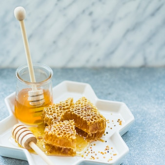 Honeycomb pieces and honey jar on floral tray