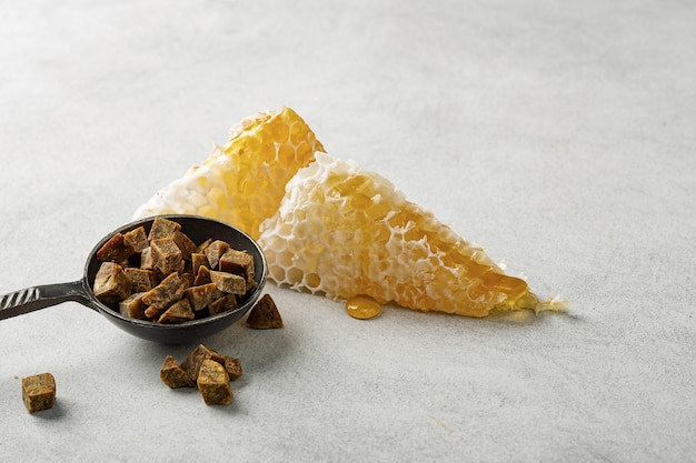 Honeycomb and propolis in an iron spoon