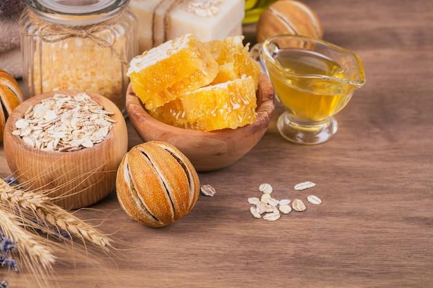 Соты, морская соль, овсяные хлопья и мыло ручной работы с медом на деревенском деревянном фоне. натуральные ингредиенты для домашней маски или скраба для лица и тела. уход за здоровой кожей. концепция спа.