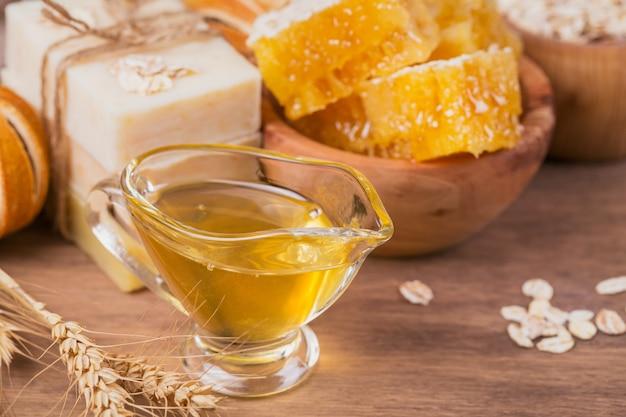 素朴な木製の背景に蜂蜜と蜂蜜、海塩、オートミール、手作り石鹸。自家製フェイシャルおよびボディマスクまたはスクラブ用の天然成分。健康的なスキンケア。 spaのコンセプト。