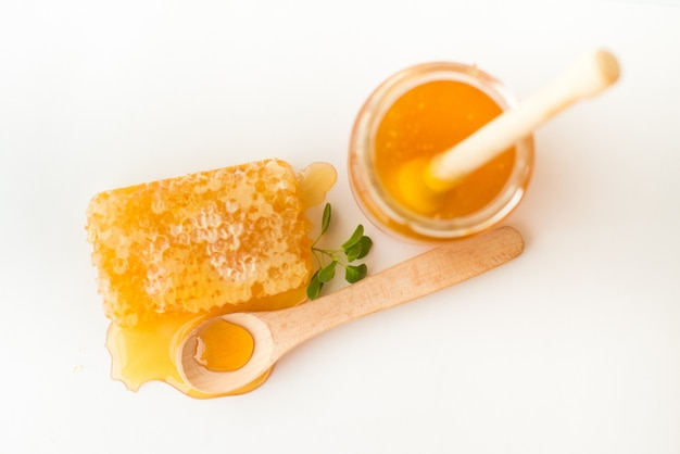 Honeycomb with herb, wooden spoon and jar