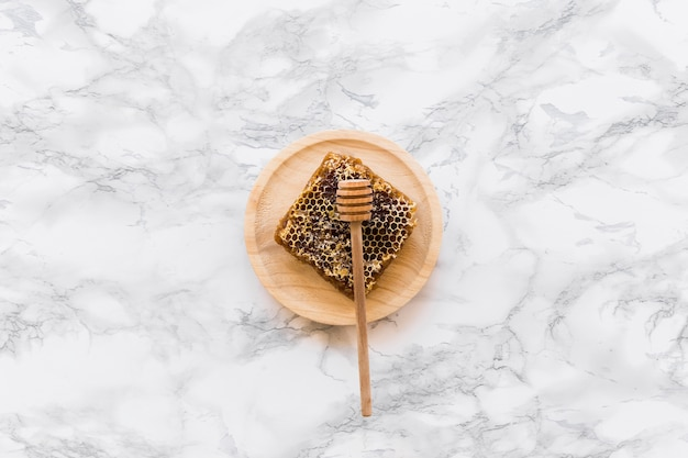 Honeycomb with honey dipper on wooden plate