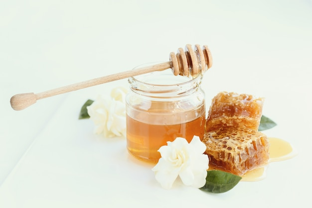 Honeycomb with jar and flowers