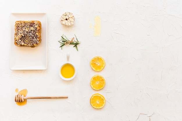 Honeycomb with lemon, rosemary and garlic on white wall background