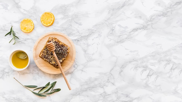 Honeycomb with olive oil on white marble background