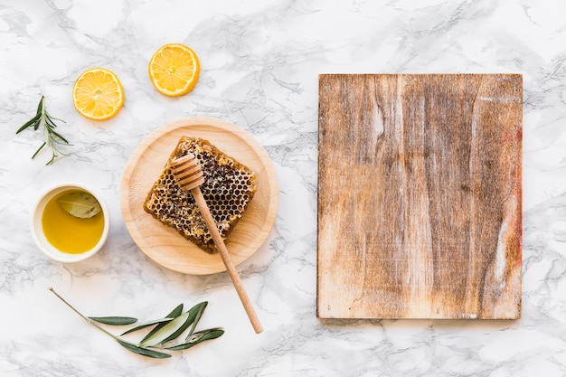 Honeycomb with olive oil with wooden chopping board