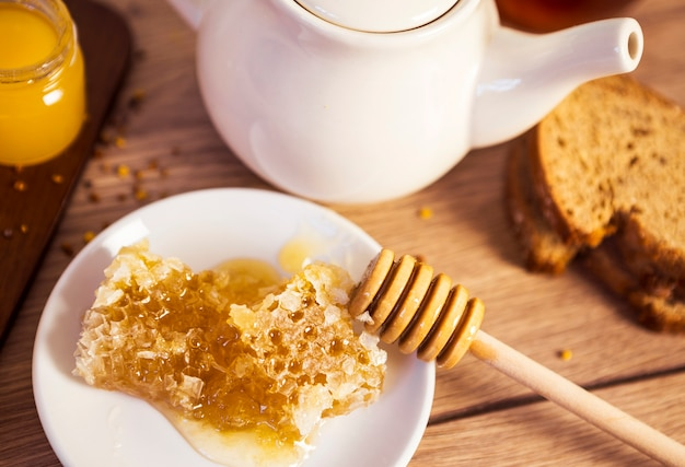 Honeycomb with tea and bread on table