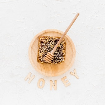 Honeycomb with wooden honey dipper on plate with text honey
