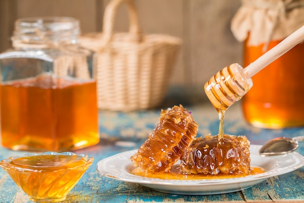 Honeycombs on plate on wooden surface.