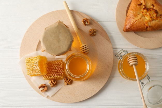 Honeycombs, walnuts, dipper, jars with honey and bun on wooden background, top view