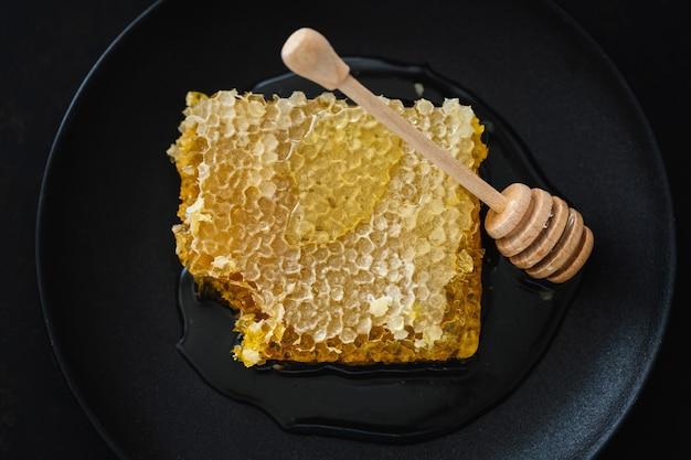 暗い背景に新鮮な蜂蜜と蜂蜜のスプーンとハニカム。閉じる