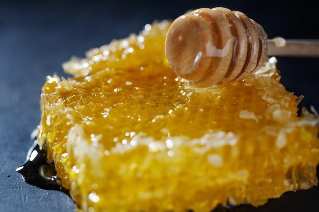 Favi con miele fresco e cucchiaio di miele su sfondo scuro. avvicinamento