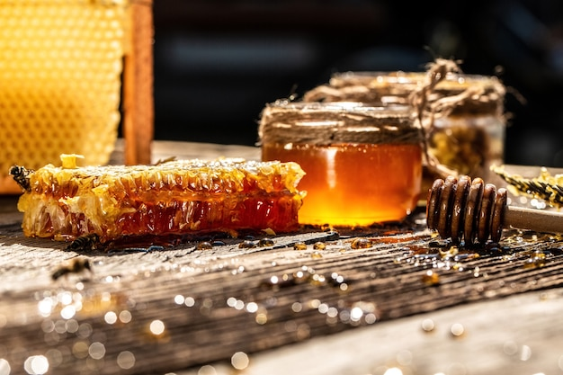 Honeycombs with full cells of honey with wooden honey dipper on wooden table