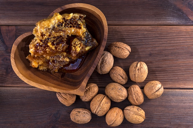 Honeycombs with honey in a wooden plate and many inshell walnuts on a wooden surface. view from above