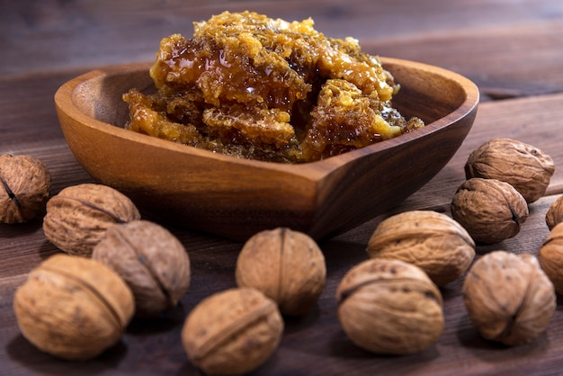 Honeycombs with honey in a wooden plate and many inshell walnuts on a wooden surface