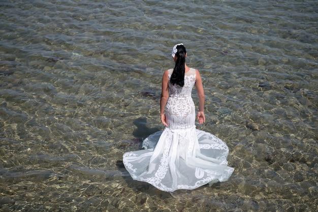 シーリゾートでのハネムーン。海外での結婚式。結婚式の海岸。花嫁の白いウェディングドレスは海の水に立っています。濡れたウェディングドレス暑い晴れた日。幸せな花嫁は夏休みの海の背景をお楽しみください。