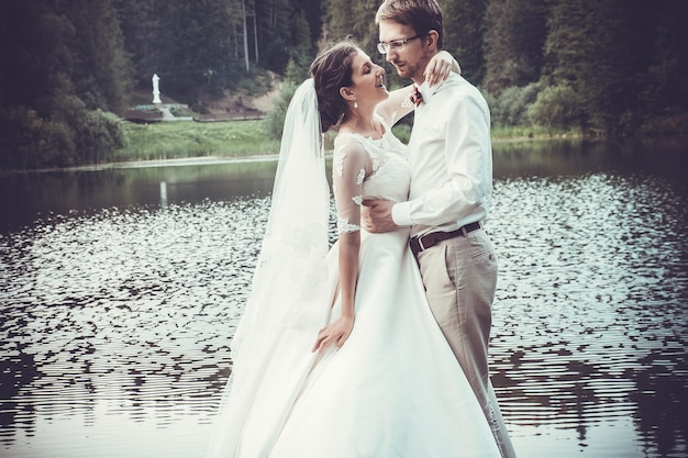 Honeymoon. the bride and groom hugging on the shore of lake.
