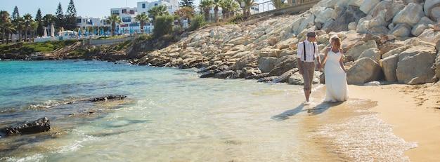新婚旅行のカップルは一緒に歩くヨーロッパの花嫁と花婿の海とビーチリゾートを旅行します