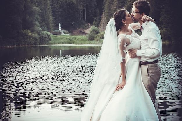 ハネムーン。湖のほとりで抱き締める新郎新婦。