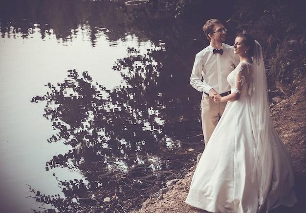 Медовый месяц. жених и невеста обнимаются на берегу озера.