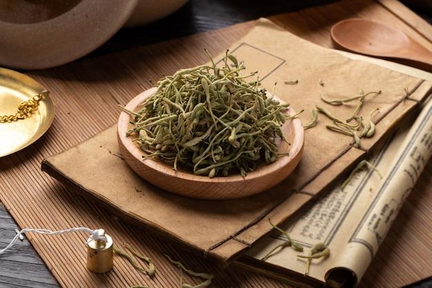 テーブルの上のスイカズラ古代漢方薬の本とハーブ