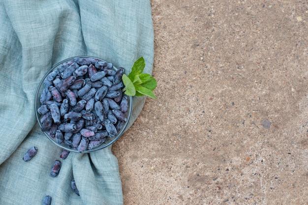 スイカズラの果実と青いリネンの布にミントの葉