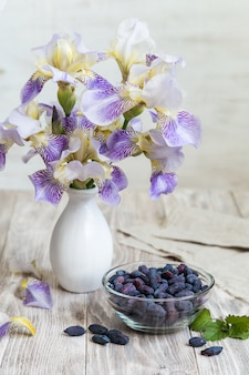 ベリーと木製のテーブルの上にスイカズラの花瓶