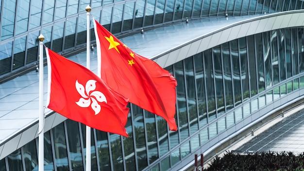 Государственные флаги гонконга и материкового китая стоят вместе с копией пространства