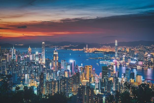 山からの夕日の景色の劇的な空に香港の街